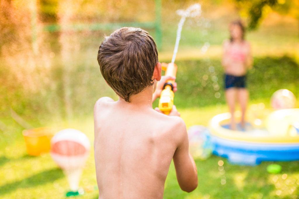 Boy splashing girl with water gun in garden swimming pool, sunny summer day, back yard,