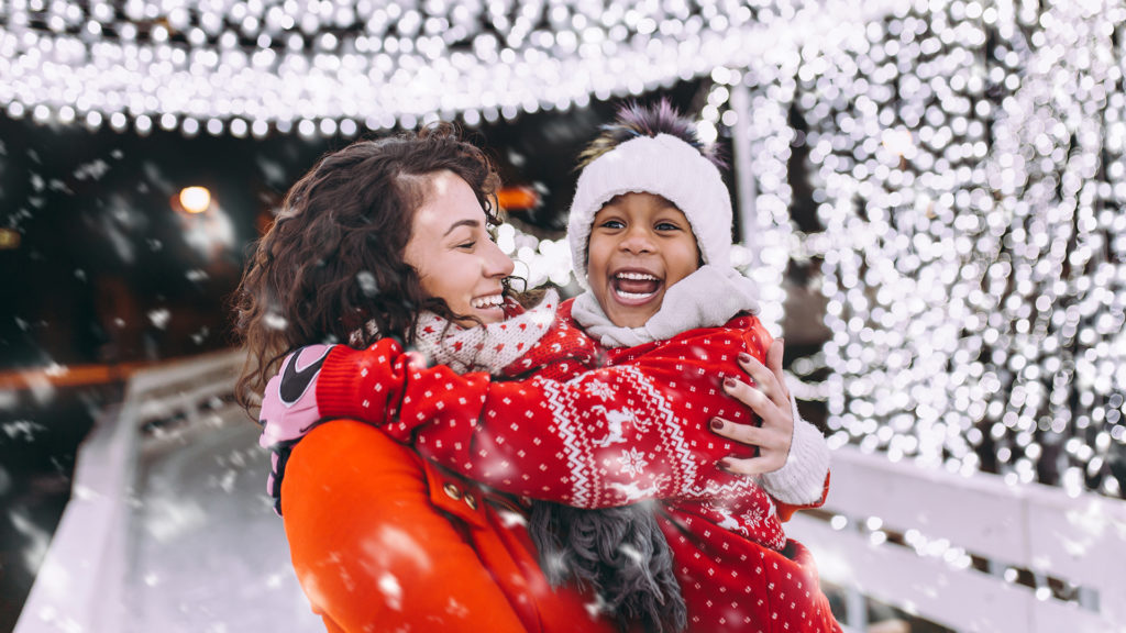 Little girl enjoying in ice skating with her mother.