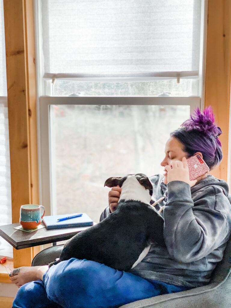 chatting on the phone, dog on lap